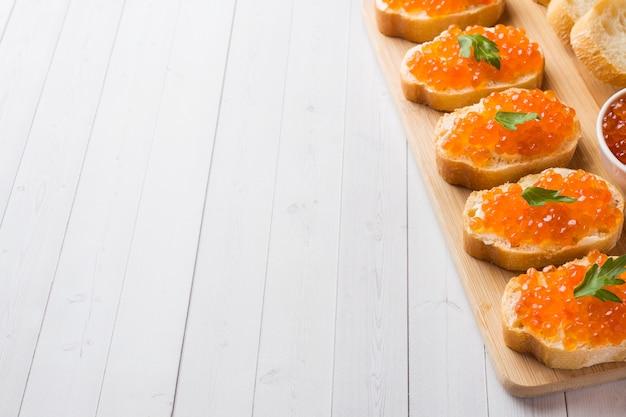 Sandwiches au caviar de saumon rouge sur une planche de bois. dessus de table blanc.