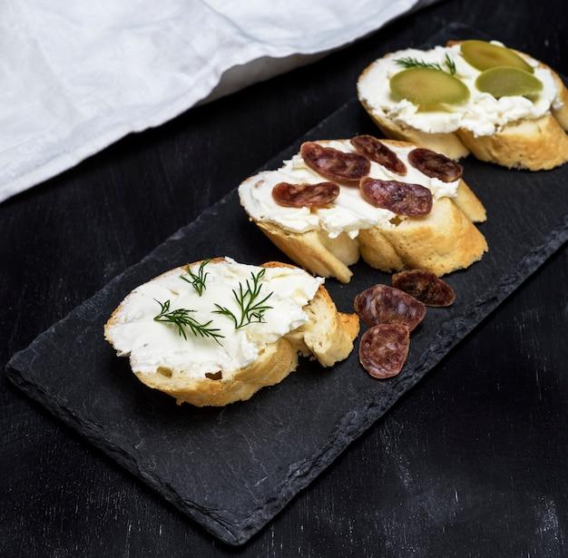 Sandwiches au fromage blanc crémeux, saucisse, olives et aneth