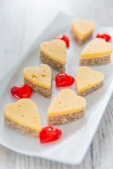 Sandwiches au fromage en forme de coeur sur une plaque blanche
