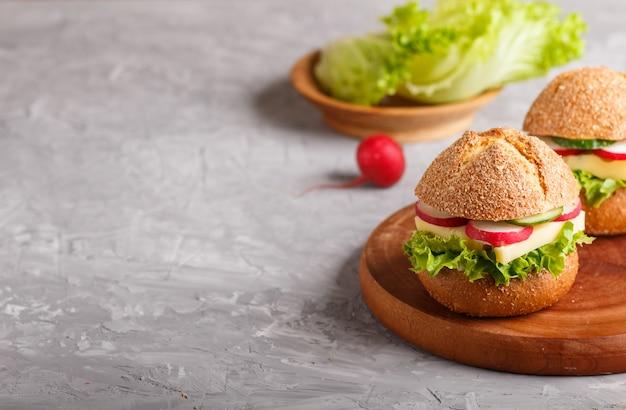 Sandwiches au fromage, radis, laitue et concombre sur une planche de bois sur un béton gris.
