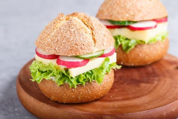 Sandwiches au fromage, radis, laitue et concombre sur une planche de bois sur un fond de béton gris.