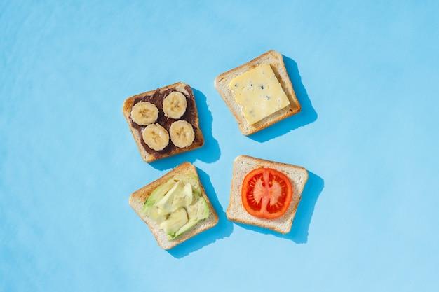 Sandwiches au fromage, tomate, banane et avocat sur une surface bleue. mise à plat, vue de dessus.