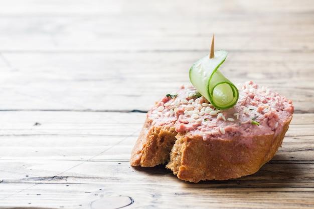 Sandwiches au pâté de poulet et concombre sur une table en bois.