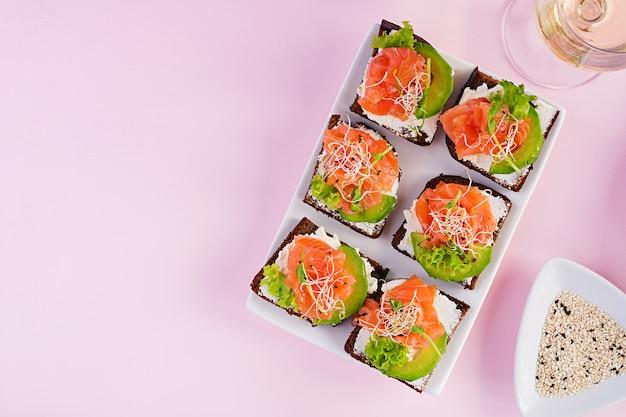 Sandwiches au saumon avec fromage à la crème et microgreen. canape au saumon.