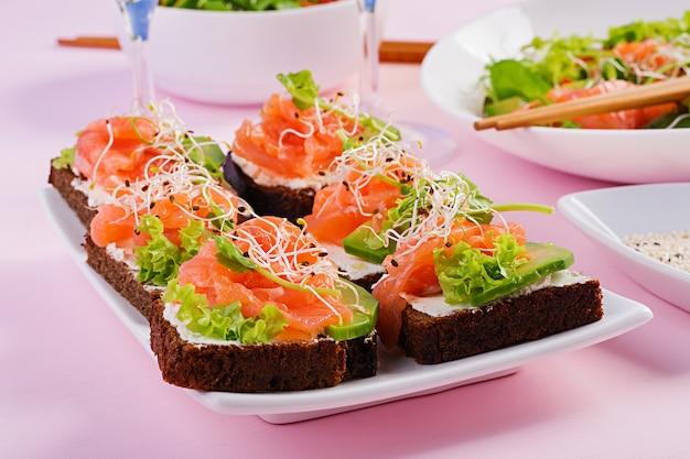 Sandwiches au saumon avec fromage à la crème et microgreen.