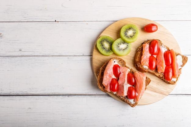 Sandwiches au saumon fumé au beurre et tomates cerises sur blanc