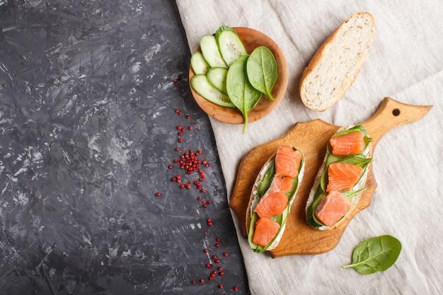 Sandwiches au saumon fumé avec concombre et épinards sur planche de bois