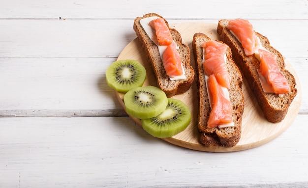 Sandwiches au saumon fumé avec du beurre sur un fond en bois blanc.