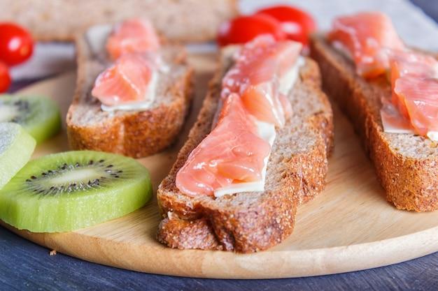Sandwiches au saumon fumé avec du beurre sur un fond en bois foncé.