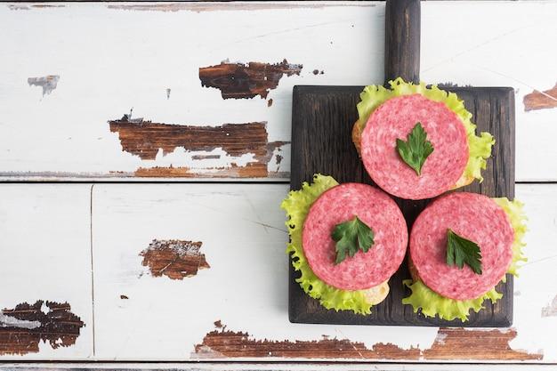 Sandwiches aux feuilles de laitue et saucisse de salami en tranches sur une planche de bois. copier la vue de dessus de l'espace