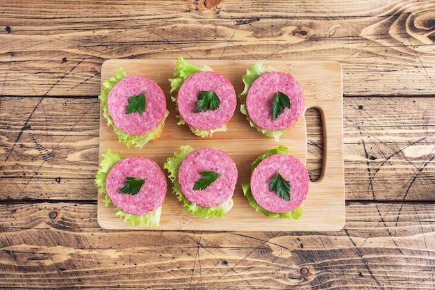 Sandwiches aux feuilles de laitue et saucisse de salami en tranches sur une planche de bois. espace copie vue de dessus
