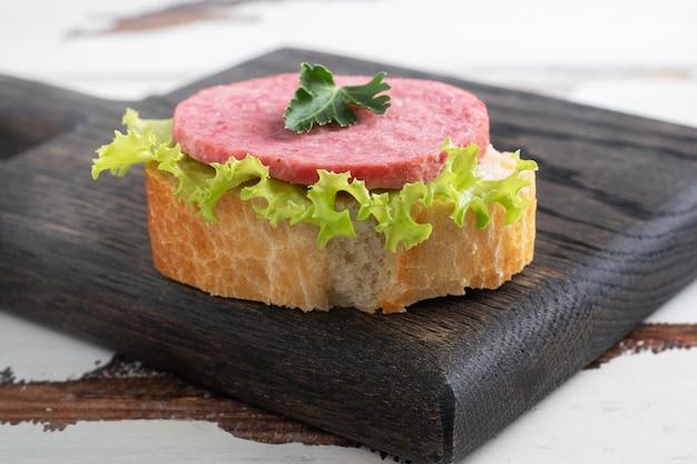 Sandwiches aux feuilles de laitue et saucisse de salami en tranches sur une planche de bois.