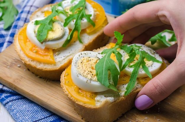 Sandwiches aux œufs durs, tomates jaunes et roquette.