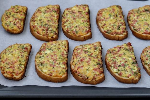 Sandwiches chauds faits maison avec du fromage et des saucisses, sur parchemin sur une plaque à pâtisserie, orientation horizontale