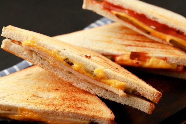 Sandwiches coupés en deux sur une planche à découper en bois avec serviette sur table