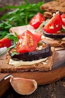Sandwiches croustillants au régime végétarien avec fromage à la crème à l'ail, aubergines grillées, roquette et tomates cerises sur une vieille surface en bois