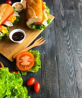 Sandwiches délicieux avec de la dinde, du jambon, du fromage et des tomates