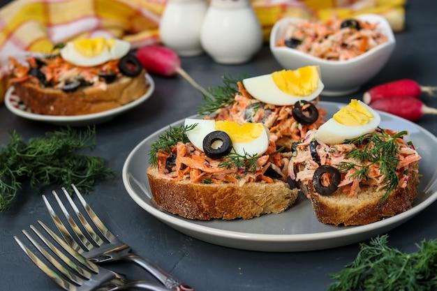 Sandwiches faits maison avec des carottes et des radis, décorés avec des œufs durs et des olives noires dans une assiette contre un sombre