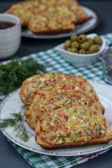 Sandwiches faits maison avec du fromage et des saucisses avant la cuisson sur du parchemin sur une plaque à pâtisserie, le processus de cuisson, l'orientation verticale