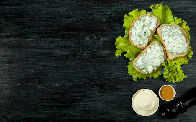 Sandwiches frais avec des légumes sur un tableau noir sur une surface texturée.