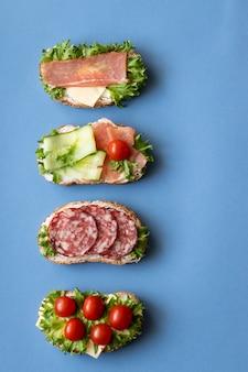 Sandwiches frais avec saucisses, fromage, bacon, tomates, laitue, concombres sur bleu