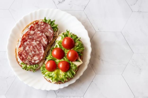 Sandwiches frais avec saucisses, fromage, bacon, tomates, laitue, concombres sur marbre