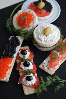 Sandwiches avec pain craquelin, caviar et légumes.