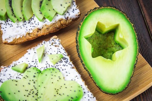 Sandwiches de pain avec des tranches, des étoiles, des coeurs d'avocat et fromage blanc sur fond en bois.