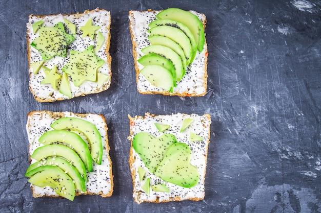 Sandwiches à partir de tranches de pain, étoiles, coeurs d'avocat et fromage blanc, fond de marbre foncé