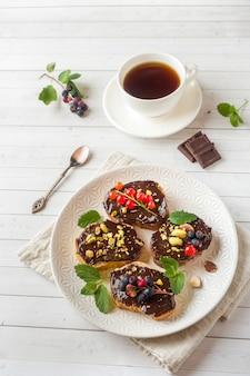 Sandwiches à la pâte de chocolat, pistaches et baies fraîches sur une assiette.