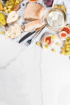Sandwiches à la ricotta ou au fromage à la crème, ciabatta, figues fraîches, poires, raisin, noix et miel sur tableau blanc, avec vue de dessus de verre à vin