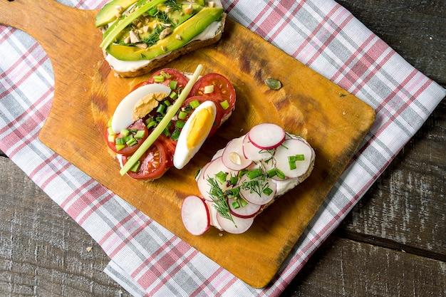 Sandwiches ou tapas aux légumes, sur une planche à découper, sur fond de bois.