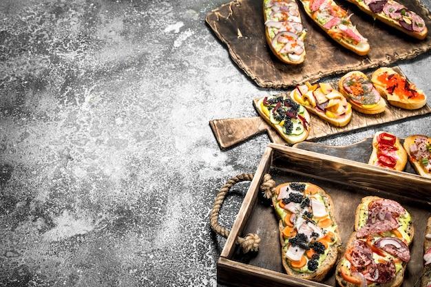Sandwiches à la viande, salami, fruits de mer et légumes frais sur table rustique.