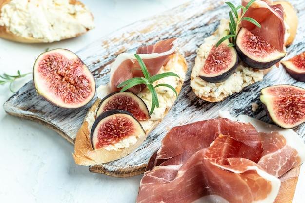 Sandwichs antipasti italiens avec jambon, fromage cottage et figues. bruschetta traditionnelle avec jambon de parme et prosciutto