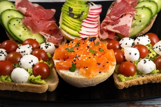 Sandwichs assortis avec du poisson, du fromage, de la viande et des légumes sur une plaque noire et une surface en bois.
