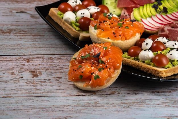 Sandwichs Assortis Avec Du Poisson, Du Fromage, De La Viande Et Des Légumes Sur Une Plaque Noire Photo Premium
