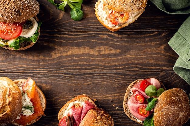 Sandwichs assortis sur une surface en bois. concept d'aliments sains avec espace de copie. vue de dessus