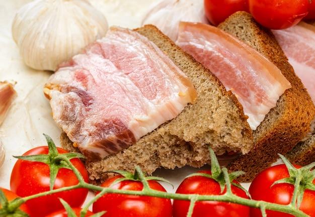 Des sandwichs au bacon salé sur du pain de seigle. avec tomates cerises et ail.