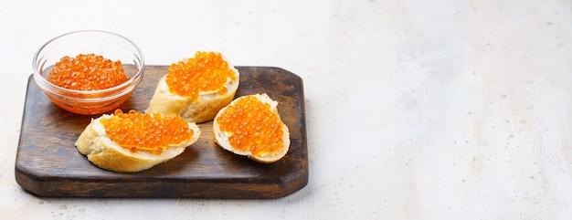 Sandwichs au caviar rouge et beurre en assiette sur table en bois. vue de dessus