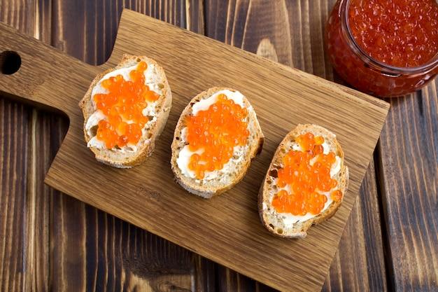 Sandwichs au caviar rouge sur la planche à découper en bois.vue d'en haut.