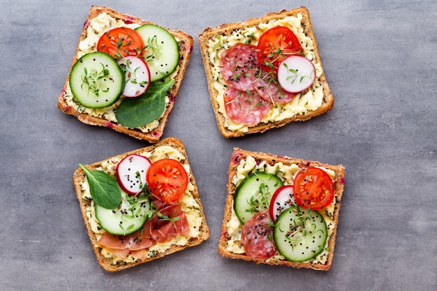 Sandwichs au fromage à la crème, légumes et salami.