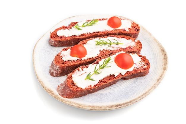 Sandwichs au pain aux betteraves rouges avec fromage à la crème et tomates isolés sur fond blanc. vue de côté, gros plan.