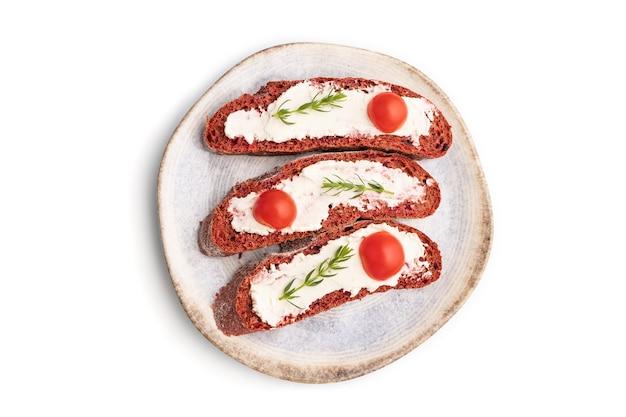 Sandwichs au pain aux betteraves rouges avec fromage à la crème et tomates isolés sur une surface blanche