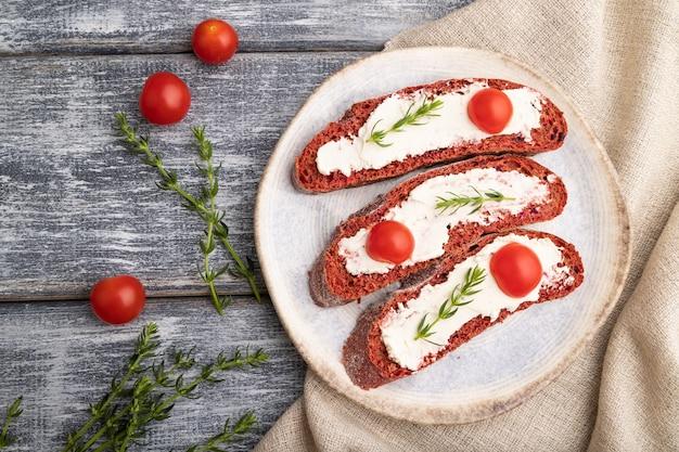 Sandwichs au pain à la betterave rouge avec fromage à la crème et tomates sur bois gris