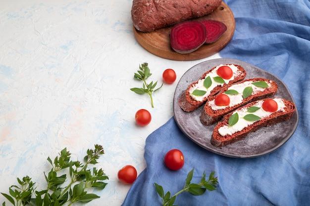 Sandwichs au pain à la betterave rouge avec fromage à la crème et tomates sur fond de béton blanc et textile en lin bleu. vue latérale, copiez l'espace, gros plan.