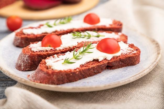 Sandwichs au pain à la betterave rouge avec fromage à la crème et tomates sur fond de bois gris et textile en lin. vue de côté, gros plan, mise au point sélective.