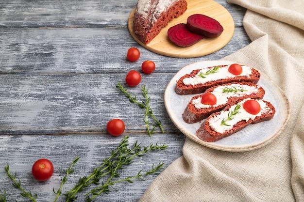 Sandwichs au pain à la betterave rouge avec fromage à la crème et tomates sur fond de bois gris et textile en lin. vue latérale, copiez l'espace.