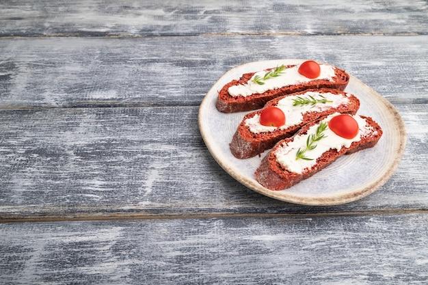 Sandwichs au pain à la betterave rouge avec fromage à la crème et tomates sur fond de bois gris. vue latérale, copiez l'espace, gros plan.