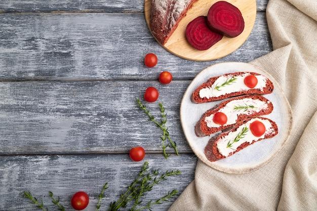 Sandwichs au pain à la betterave rouge avec fromage à la crème et tomates sur une surface en bois gris et textile en lin