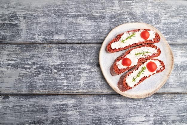 Sandwichs au pain à la betterave rouge avec fromage à la crème et tomates sur une surface en bois gris